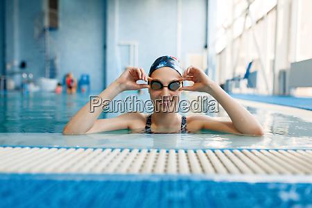 schwimmerin im badeanzug badekappe und brille