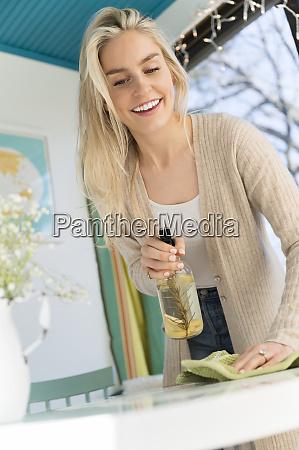 laechelnde frau reinigung tischplatte mit natuerlichen