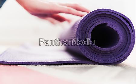 frau hand rollen yoga matte