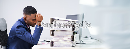 workaholic geschaeftsmann mit kopfschmerzen und stress