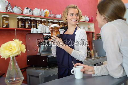 junge weibliche barista serviert kaffee zu