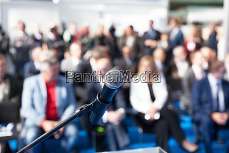 mikrofon im fokus gegen verschwommenes publikum
