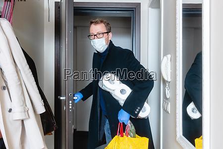 mann mit medizinischer maske kommt vom