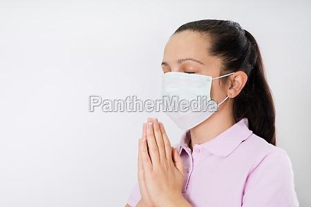 frau in handschuhen und gesichtsmaske beten