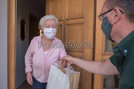 seniorin bekommt einkaufstasche von nachbarschaftshilfe