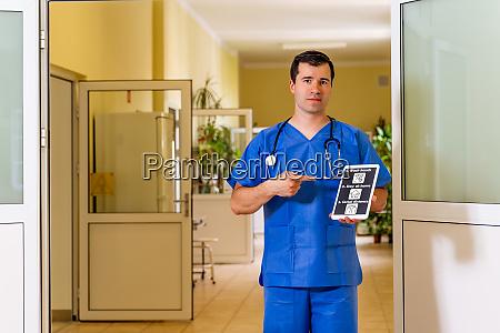 maennlicher arzt steht im krankenhaus mit