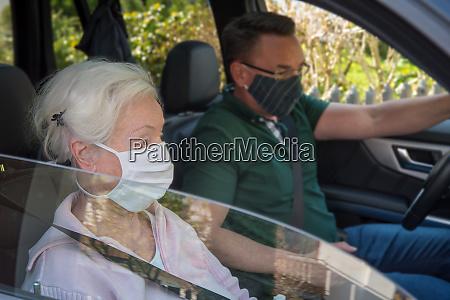 seniorin und sohn mit gesichtsmasken im