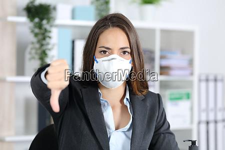 executive mit maske gestikulieren daumen nach