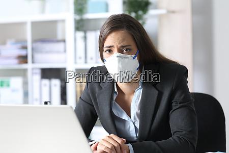 sad executive wearing mask looking at