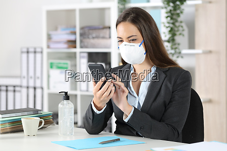 executive with protective mask using phone