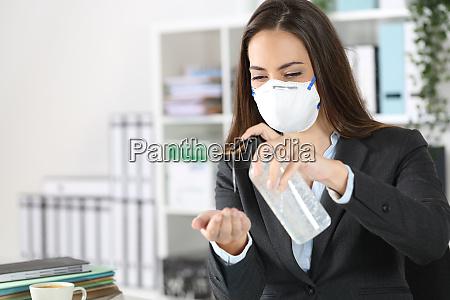 executive wearing mask using hand sanitizer