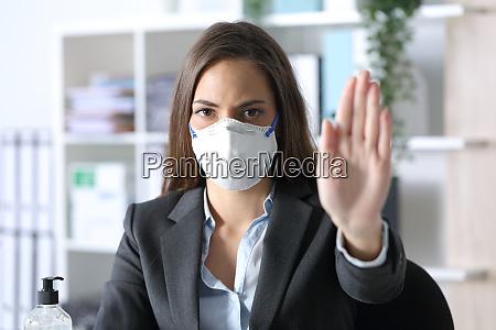 exekutive traegt maske tun stop geste