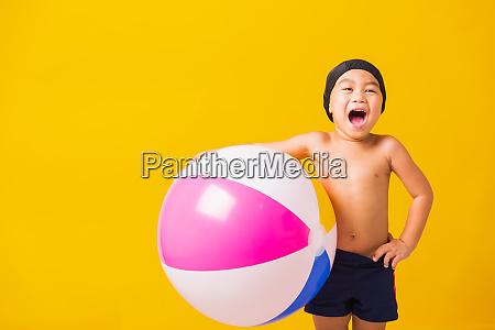 kind junge laechelnd in badeanzug halten