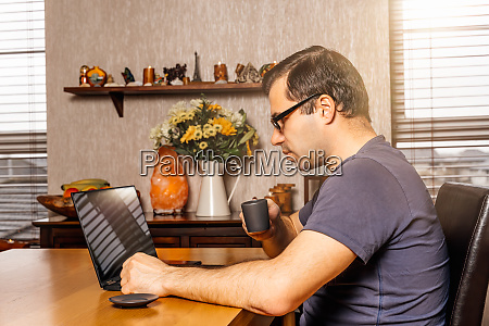 man working on laptop from comfort