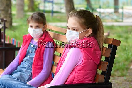 zwei maedchen in medizinischen masken sitzen
