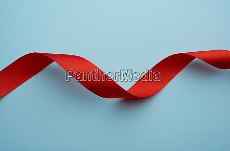 verdrehte seide rotes band auf blauem