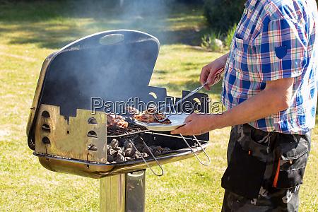 ein mann am holzkohlegrill grillt steaks