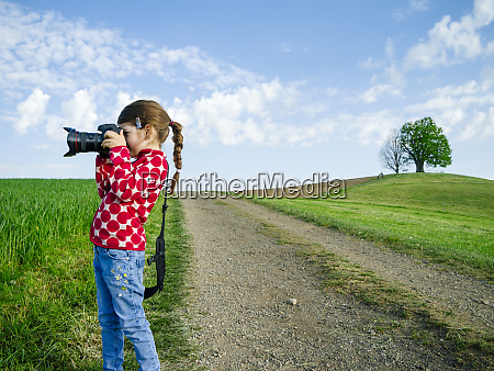 young girl with big camera in