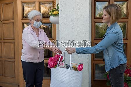 seniorin mit schutzmaske bekommt einkaufstasche vom