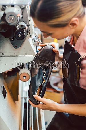 woman cobbler working on machine in