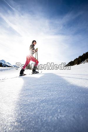 junge frau schneeschuhwandern in hohen bergen
