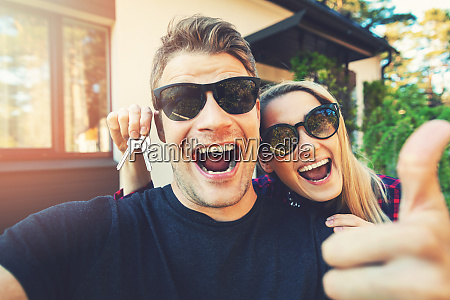 young happy couple with keys in