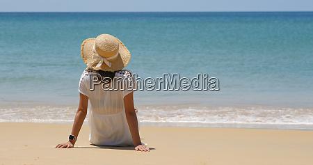 frau sitzen am strand geniessen meerblick