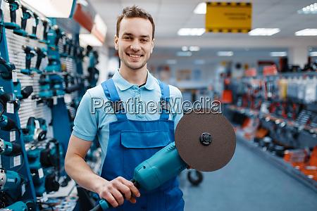 maennlicher arbeiter haelt winkelschleifer im werkzeuglager