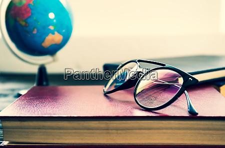 brillen und buecher neben dem fenster