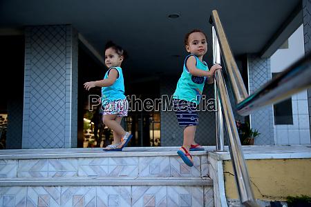 kind geht treppe am handlauf hinunter