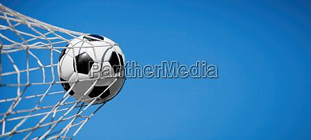 fussball im netz eines tores fussballkonzept