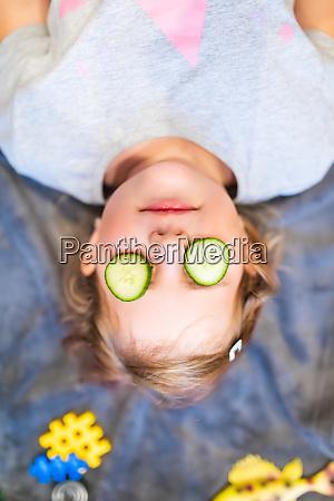 lustiges kleines maedchen mit stueck gurke