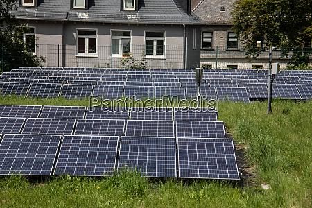 wiese mit solarzellenfeld zur stromerzeugung mit