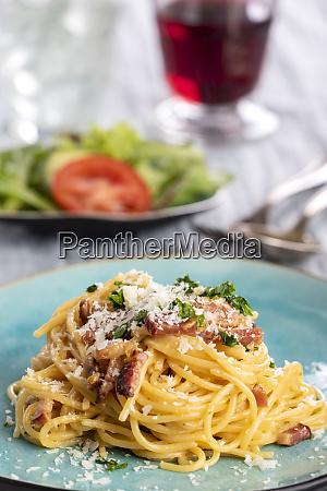 spaghetti carbonara auf einem blauen teller