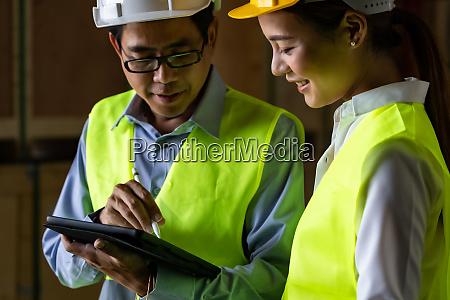 asiatischer lagerleiter im gespraech mit worker