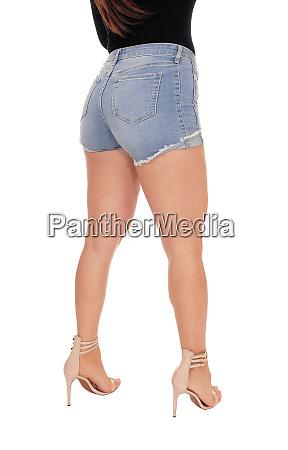 frau steht von hinten in jeansshorts