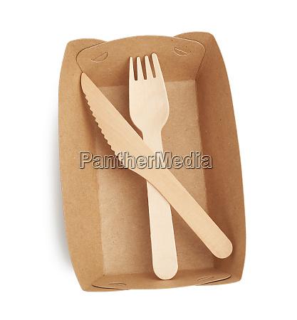 papierteller aus braunem handwerkspapier und holzgabeln