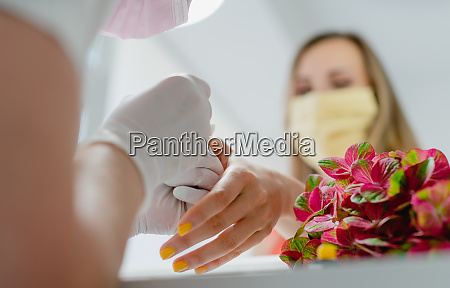 kunde im nagelkunststudio mit einer schuetzenden