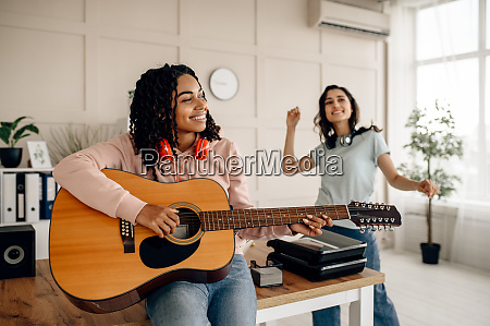 frauen spielen gitarre und hoeren musik