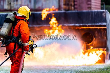 feuerwehrleute spruehen brandflamme nach OEltankwagenunfall