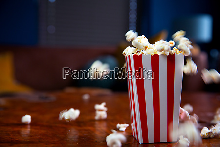 popcorn fliegt aus pappkarton rot weiss