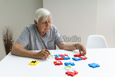 elder man spielt puzzle