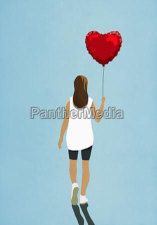 frau traegt herzform helium ballon