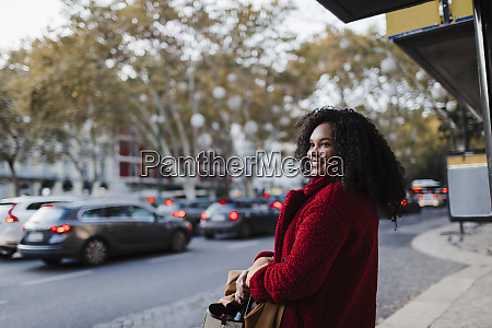 smiling young woman on urban sidewalk