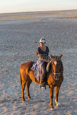 eine frau zu pferd bei sonnenuntergang