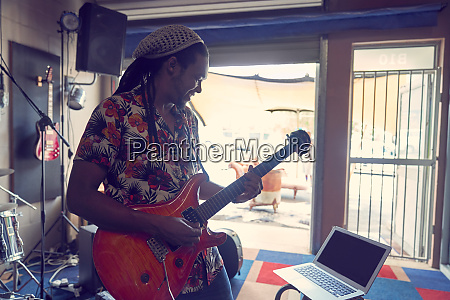 male musician with laptop playing guitar