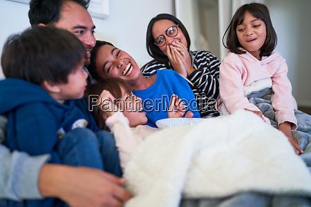 glueckliche familie lacht auf dem sofa