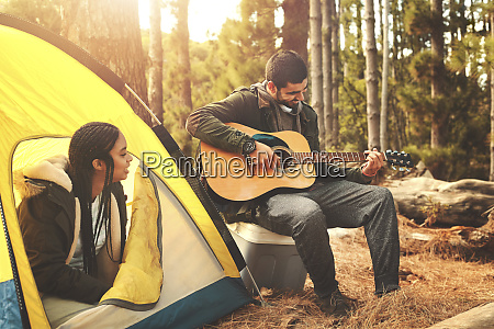 young couple playing guitar at tent