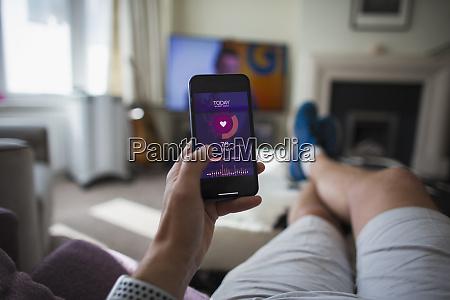pov mann ueberprueft gesundheitsstatistiken auf smartphone