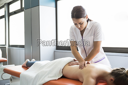 weibliche physiotherapeutin massiert den ruecken einer
